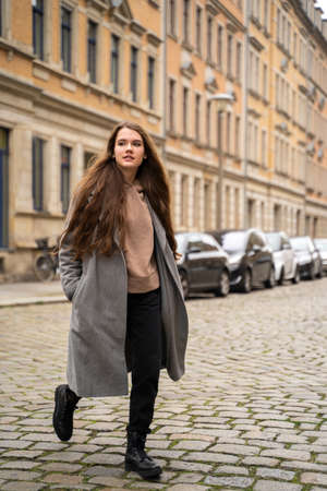 Portrait of young brunette caucasian woman dressed casually in brown hoodie and coat walking on street near residential houses and cars on cloudy early autumn day. Holiday, leisure, lifestyle