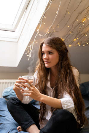 Young brunette woman in cozy warm casual clothes sitting on bed with blue cloth dreaming and drinking hot water or tea in home bedroom near pumpkin, lights and window on cloudy autumn weekend day