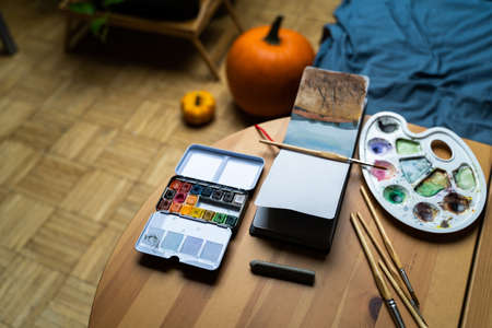 Multicolored watercolors, brushes and palettes lie on the table next to paper notebook with drawings of nature landscapes in home bedroom or studio with daylight on autumn day. Art, hobby, education Zdjęcie Seryjne