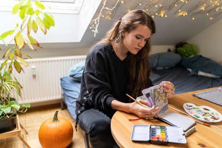 Young caucasian brunette woman drawing nature landscape on paper notebook with colorful watercolor palettes and brushes in home bedroom, sitting on bed near table and pumpkin on autumn weekend day