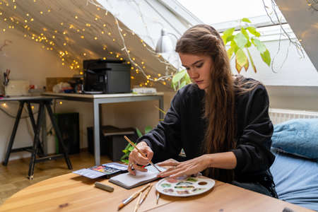 Young brunette woman student drawing nature landscape in paper notebook with colorful watercolor palettes and brushes in dormitory bedroom, sitting on bed near table and pumpkin on autumn weekend day
