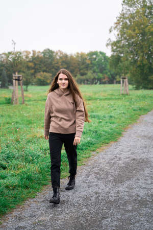 Portrait of young brunette woman dressed casually in brown hoodie walking in green fresh park with wet grass on rainy early cloudy autumn day looking into camera. Holiday, leisure, lifestyle