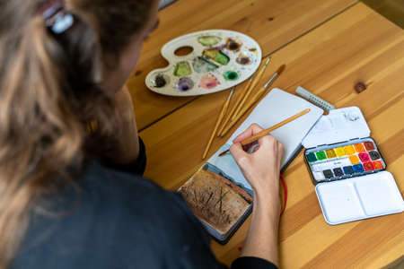 Young brunette woman having fun drawing landscape with colorful watercolor palettes and brushes in home bedroom sitting on bed near table and pumpkin on autumn weekend day. Hobby and leisure. Close up