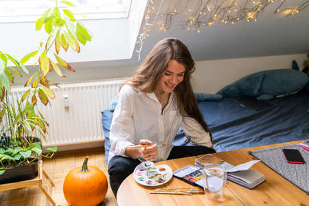 Young smiling brunette woman having fun drawing landscape with colorful watercolor palettes and brushes in home bedroom sitting on bed near table and pumpkin on autumn weekend day. Hobby and leisure Zdjęcie Seryjne