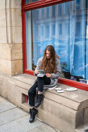 Young brunette woman dressed casually in warm coat holding paper notebook painting picture with watercolor sitting outside near window on street on cloudy autumn day. Holiday, leisure, art and hobby