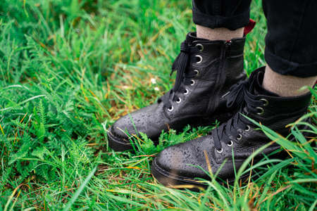 Young woman wearing black leather warm wet boots standing on green fresh grass in forest or park on rainy cloudy early autumn september or october day. Holiday, leisure, lifestyle and fashion