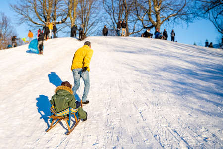 Young middle-aged father in yellow jacket and jeans carries wooden sled with his little son in warm winter clothes to crowdy snowy hill to sledge in park on sunny winter day. Holidays, parenthood Zdjęcie Seryjne
