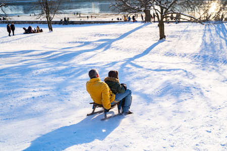 Young father and his little son in warm clothes slide down the snowy hill on wooden sled on sunny winter christmas day near river on sunset in Dresden. Holidays, family, leisure activity, childhood