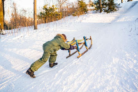 Little boy in warm winter green clothes pushing handmade wooden sled up a snowy mountain slide in park or forest on sunset. Active lifestyle, childhood, leisure activity, seasons specific, fun