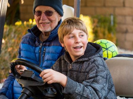 teen golf: Adolescente que conduce el carro de golf con su abuelo