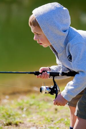 Young boy concentrates while fishing in a pond