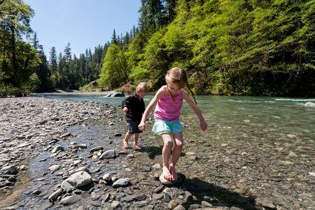 Spelende kinderen op blote voeten in het water, South Fork Trinity River, Noord-Californië Stockfoto