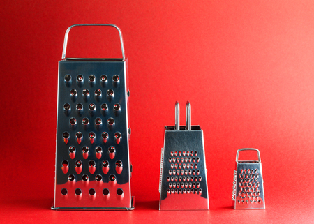 Three Different Size Graters in Order on Red Background Archivio Fotografico - 123345803