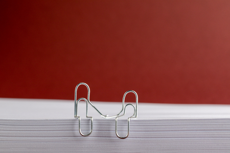 Paper Clips Holding Hands on Paper Pile on Red Background Archivio Fotografico - 123345806