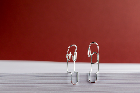 Paper Clips on Red Background Looking Sad Archivio Fotografico - 123345808
