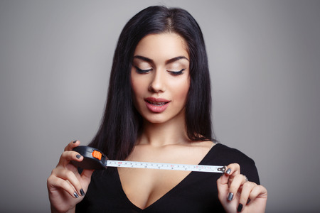 Penis Size Concept. Woman with Measuring Tape photo