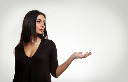 Beautiful Woman Holfing Something. Young Female Pointing to Empty Space photo