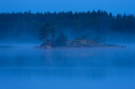 finnish: Blue colored fog surrounding a small rocky island with a thick forest on the background before sunrise on the Lake Saimaa in Puumala, Eastern Finland, Europe