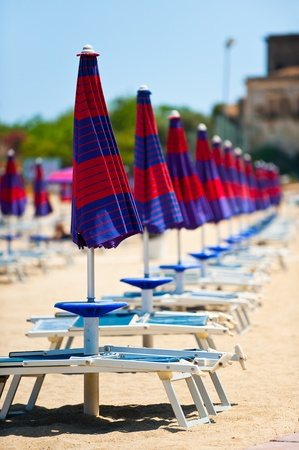 naxos: Sequence of colorful closed parasols and beech chairs on the beach of Giardini Naxos, Sicily, Italy