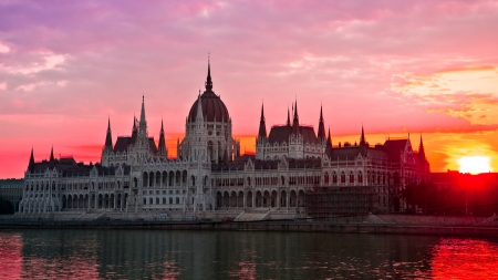 budapest: The House of Parliament, Budapest, Hungary, bathing in red morning light on eastern banks of River Danube
