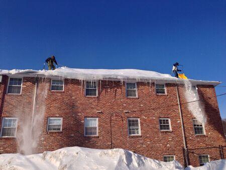 Men clearing rooftop snow Zdjęcie Seryjne