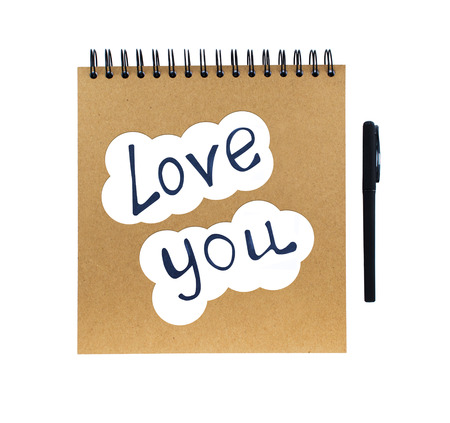 small paper: I love you written on small paper sheets and notebook with pen