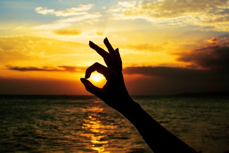 handsign: Ok hand sign silhouette at sunset. On bright sun background.