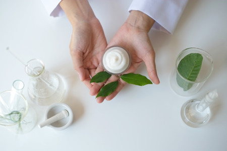 the scientist,dermatologist testing the organic natural product in the laboratory.research and development beauty skincare concept.blank package,bottle,container .cream,serum.hand