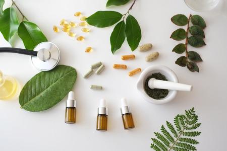alternative medicine herb , mortar, laboratory glassware, plant in tube, flower , on white background. Foto de archivo