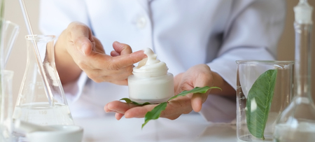 scientist hand giving  with leaves,equipment,glassware,cosmetic bottle.health and beauty natural organic product concept.herbal medicine. making cosmetic on table.