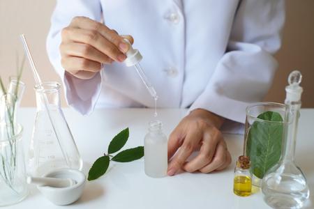 Wissenschaftlerhand gießen, lassen Öl oder Serum im Labor mit Blättern, Ausrüstung, Glaswaren, kosmetischer Flasche fallen Natürliches Bioproduktkonzept der Gesundheit und der Schönheit Kräutermedizin. Kosmetik auf dem Tisch machen.