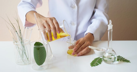 scientist hand pour,drop oil or serum in the laboratory with leaves,glassware,cosmetic bottle.health and beauty natural organic product concept.herbal medicine. making cosmetic on table.close up.