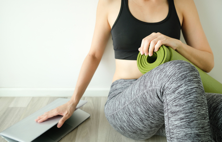 woman stop to work and workout or fitness at home for balance idea. close computer hold yoga mat. balancing life concept.