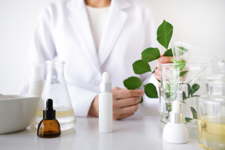 the scientist,dermatologist make the organic natural herb cosmetic product in the laboratory. beauty healthy skincare concept. herb medicine ,blank package,bottle,container.cream,serum. Stock Photo
