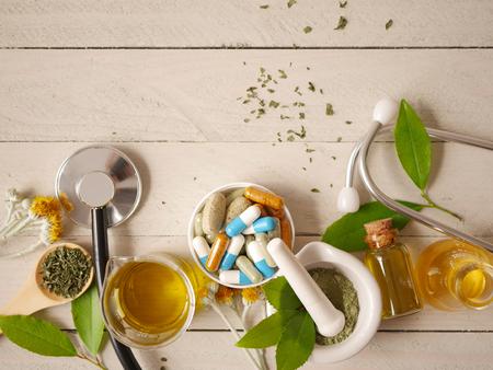 alternative Medizin Kräuterbehandlungskonzept. Herde mit Mörser- oder Holztischdraufsicht. Kapsel- und Lösungsmedizin. Standard-Bild