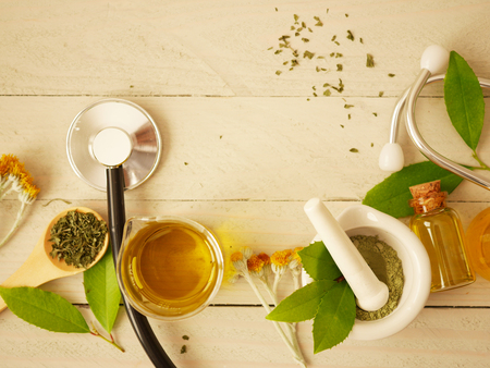 alternative medicine herbal treatment concept. herd with mortar or wooden table top view. capsule and solution medicine.