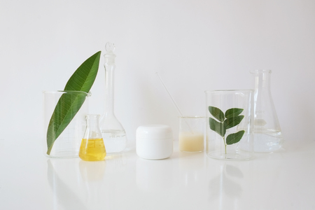 skincare and cosmetic package with laboratory glassware and leaf  for natural beauty and organic skincare on white background. Stock Photo