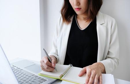 schöne junge Geschäftsfrau, die im Büro oder zu Hause mit Papierkram-Rechner-Laptop und -computer arbeitet.