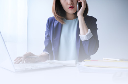 beautiful young business woman working in the office or home with paperwork calculator laptop and computer.