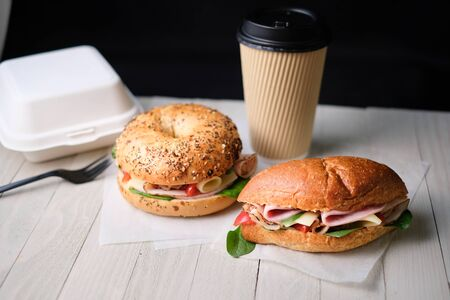 Delicious classic blt sandwiches with ham, cheese, bacon, tomatoes. Breakfast and fast food meal box set with drink on isolated black background wooden and text copy space.