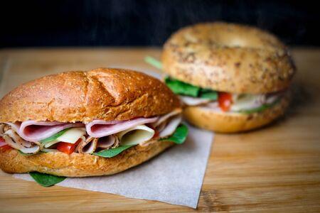 Deliziosi panini classici blt con prosciutto, formaggio, pancetta, pomodori. Colazione e pasto veloce. su sfondo nero isolato in legno e lo spazio della copia del testo.