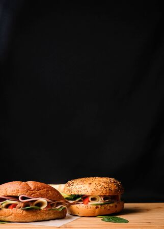 Delicious classic blt sandwiches with ham, cheese, bacon, tomatoes. Breakfast and fast food meal. on isolated black background wooden and text copy space.