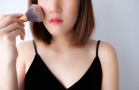 Young beautiful woman applying make up.