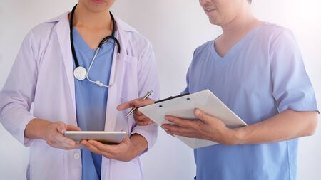 two doctor discus in the medical hospital by using tablet. healthcare and wellness living. blue uniform.hospitality concept.