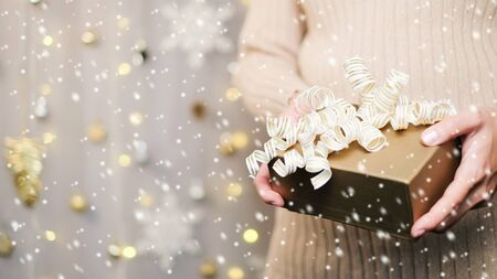 Hand hold gift for Christmas and new year background banner with the beautiful decor for holiday in winter. On bright blue, golden and silver color theme with snow flake. top view with copy space. 版權商用圖片