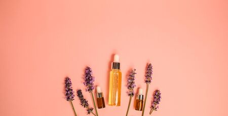 skin care product on pink flat lay backgroung . organic beauty essential oil with herbal and lavender.aromatheraphy for wellness and sp concept.