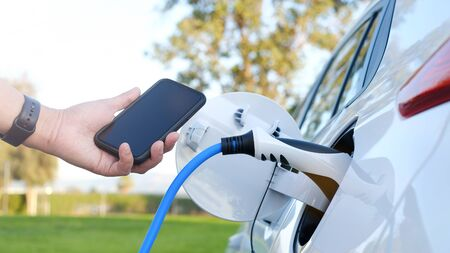 Electric car or ev is charging at station . man use the white power cable and plug on nature background. eco and clean energy concept with the mobile phone smart technology. zero gas and no transmission. 版權商用圖片