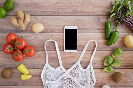 mobile phone with the net eco bag and fresh vegetable on wood background. online grocery and organic farmer product shopping application. food and cooking recipe or nutrition counting.flat lay. Imagens