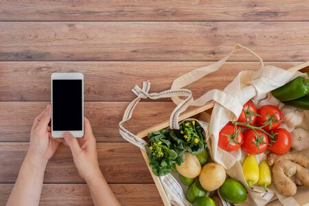 mobile phone with fresh vegetable in the wood box. online grocery and organic farmer product shopping application. food and cooking recipe or nutrition counting.flat lay.