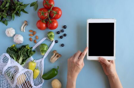 hand use digital tablet with the eco bag and fresh vegetable. online grocery and organic farmer product shopping application. food and cooking recipe or nutrition counting.flat lay. Imagens